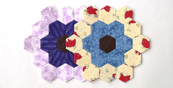 Top view of two hexagon flower blocks, one in bright primary colors and the other in purples, on a white background.