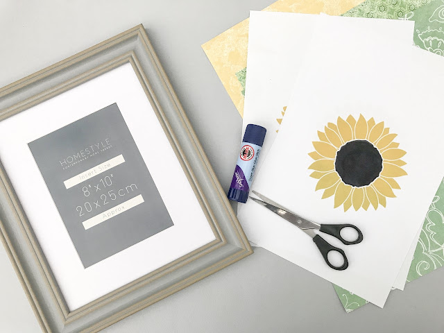 Flatlay showing picture frame, sunflower design on paper, glue and scissors