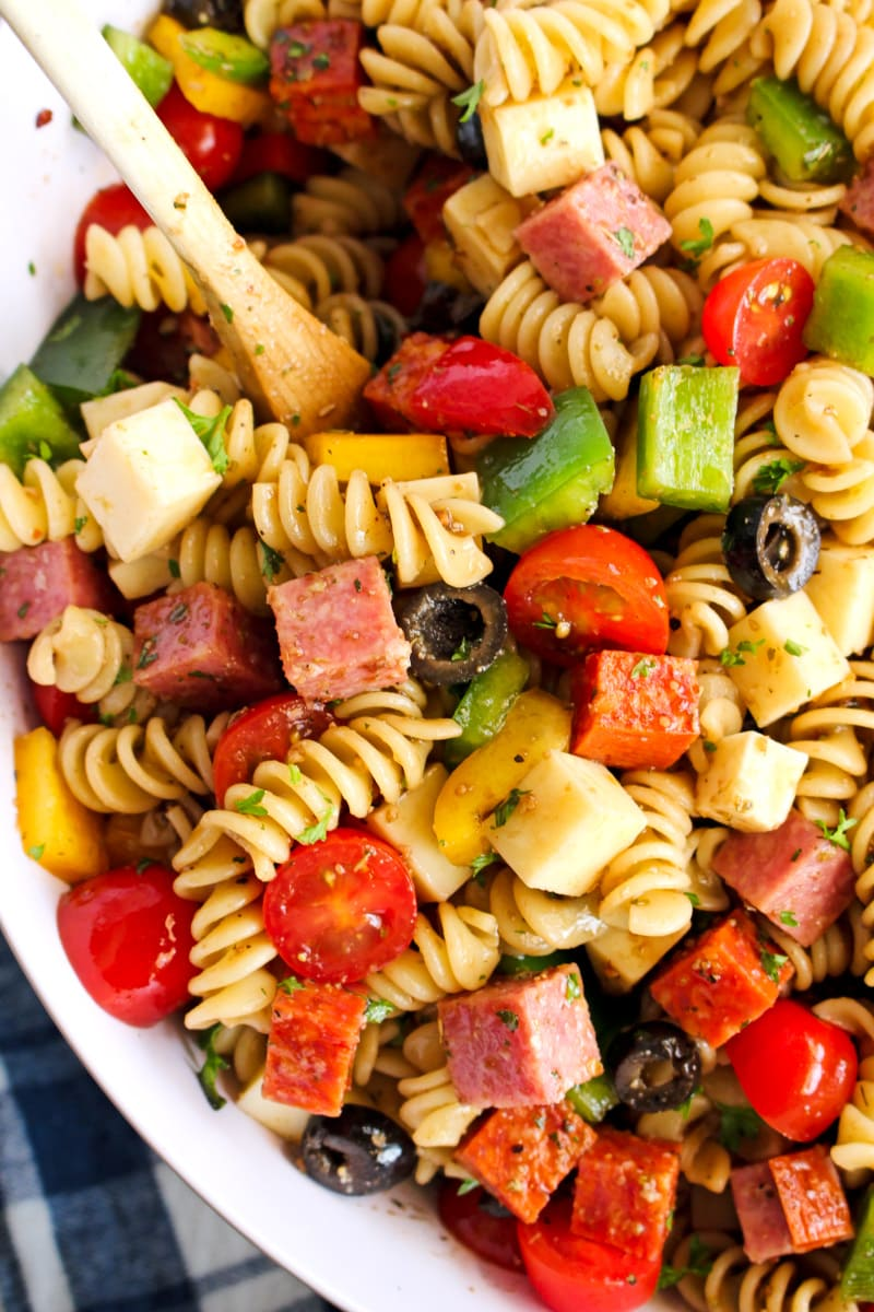 Close up top view of Manhattan Deli Pasta salad in a white bowl on a white wood background.
