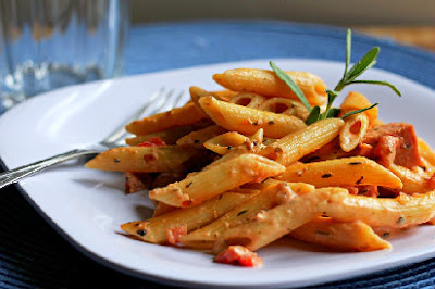 creamy penne sausage pasta with a sprig of rosemary on a white plate