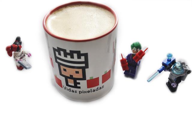 la taza con el logo de Vidas Pixeladas, rodeada de figuras de lego de Harley, Joker y Mr Freeze