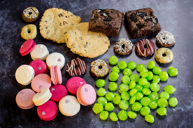 A selection of delicious vegan gift foods from Yumbles including Vegan Love Heart Macarons in shades of pink and mixed vegan treat box including cookies, mini doughnuts and chocolate oreo brownies and hard boiled green sweets