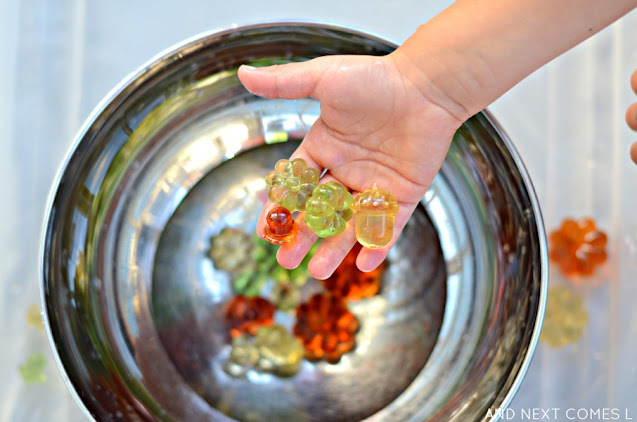Fall sensory bin activity with water, pumpkins, and acorns