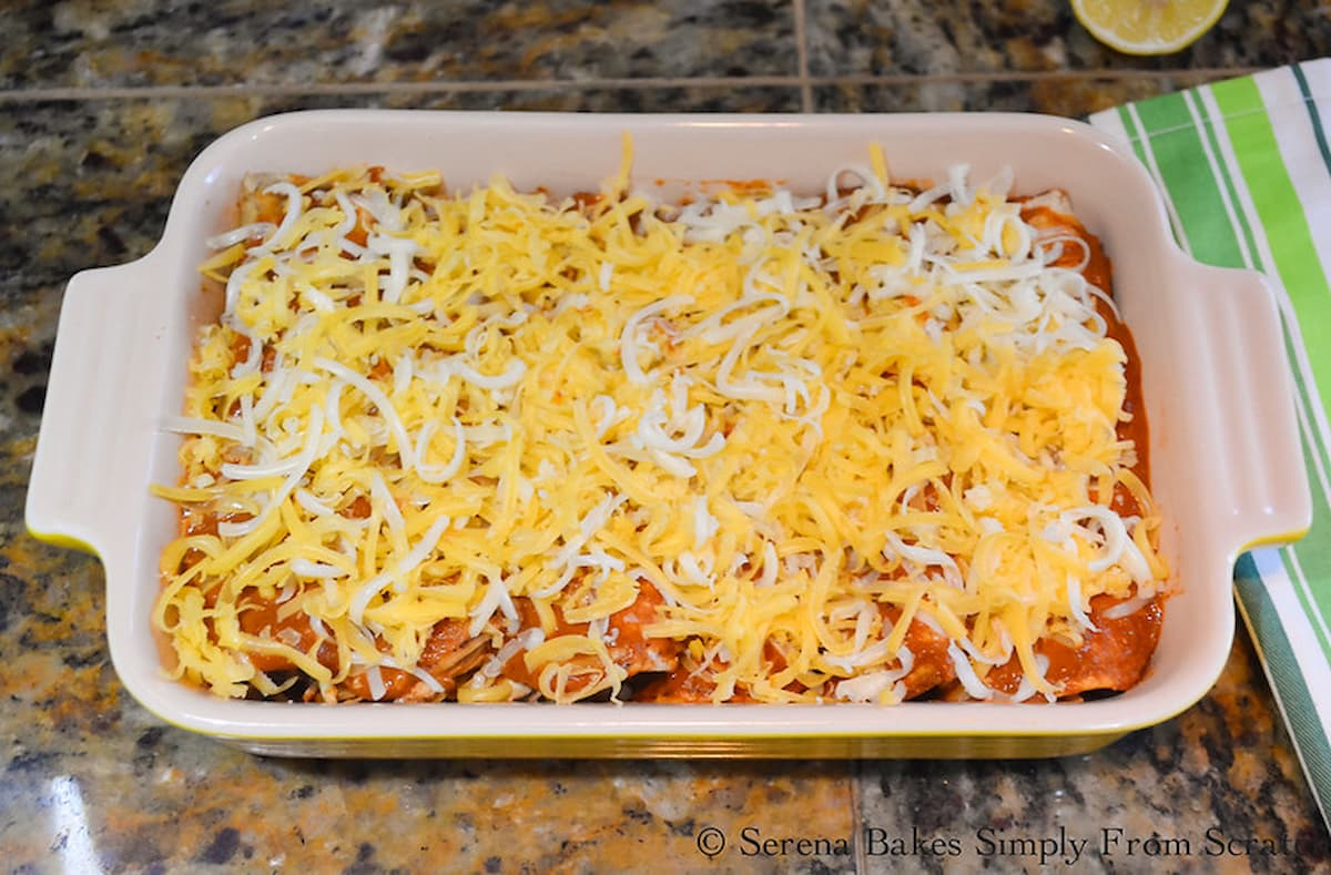 Chicken Enchiladas in Red Enchilada Sauce covered with shredded cheese in a baking pan.