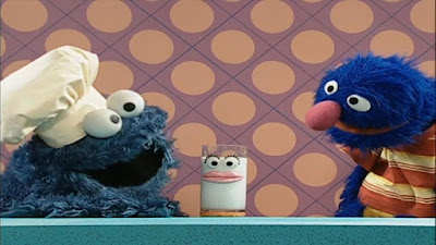 Cookie Monster prepares a glass of milk as a healthy snack to Grover. Sesame Street Happy Healthy Monsters