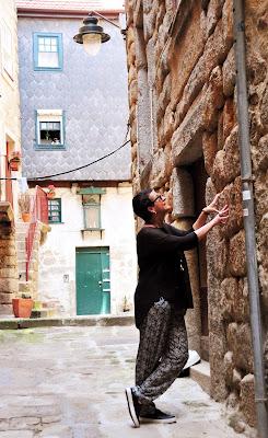 Rita Branco com suas mãos sobre as pedras de granito das paredes das casas do Porto