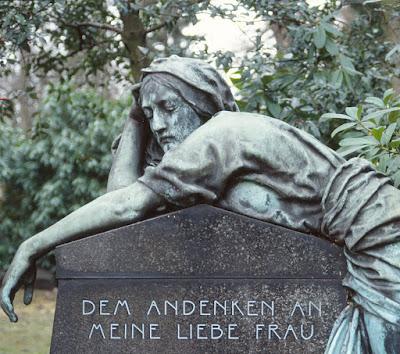 Trauernde Frauenfigur lehnt über Grabmal