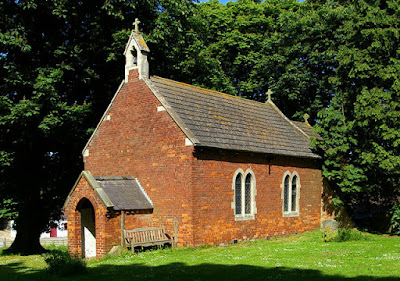 small red brick church with concrete tiled roof and bellcote, two pairs of lancet windows at the side