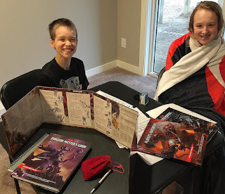 Two children, a boy and a girl, each within a couple of years of age ten by appearances, smiling and laughing at a table covered with Dungeons and Dragons paraphernalia.