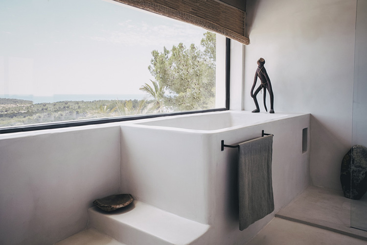 Minimalistic rustic bathrooms with a dreamy calm vibe in Ibiza, design by Hollie Bowden | Tadelakt bathroom, stucco bathroom, minimalist rustic bathroom, built-in bathtub, built-in shower, concrete bathroom, modern country bathroom, contemporary rustic bathroom
