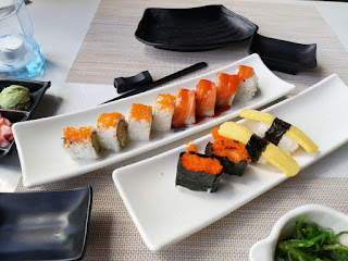 Two rectangular white plates filled with rectangular sushi with pink and red rectagnaulr strips on top on a large white table on a bright background