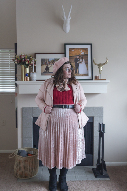 An outfit consisting of a pink beret, a pink faux leather peplum jacket, a pink bow scarf, a red sweater tucked into a pink faux velvet skirt.
