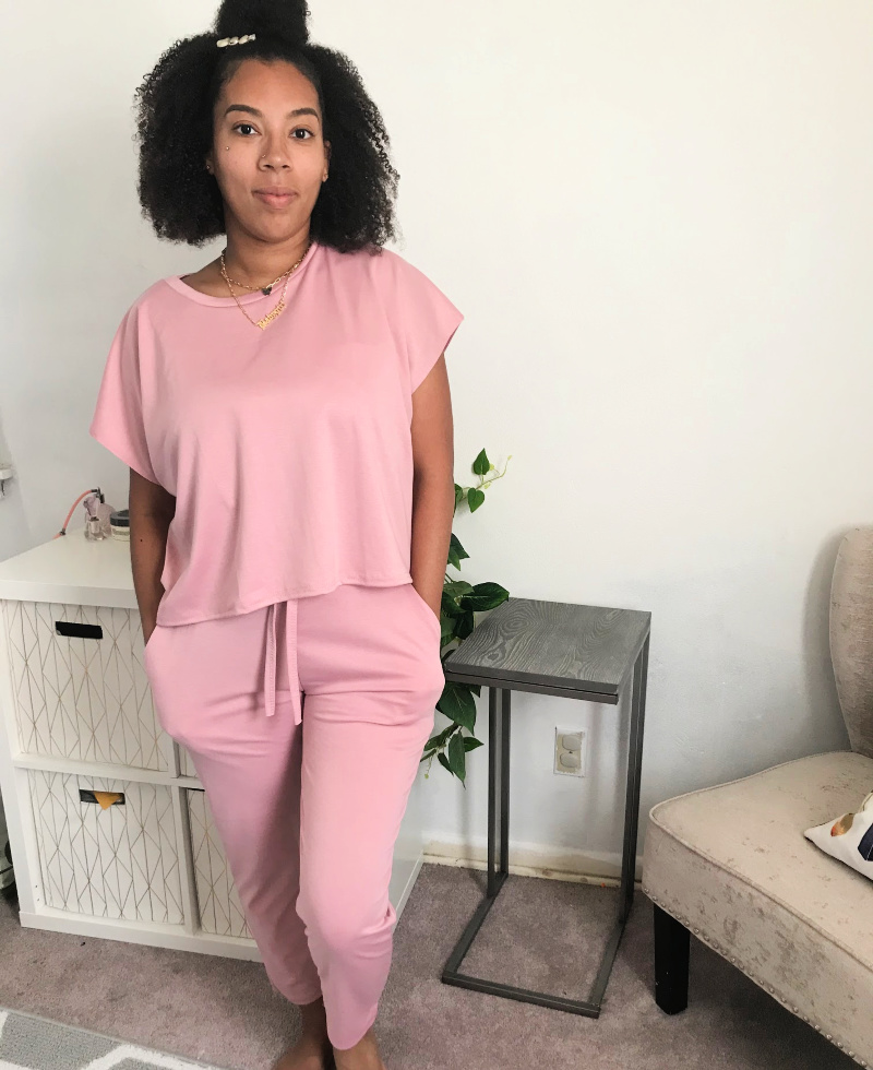 a black woman wearing a pink lounge suit
