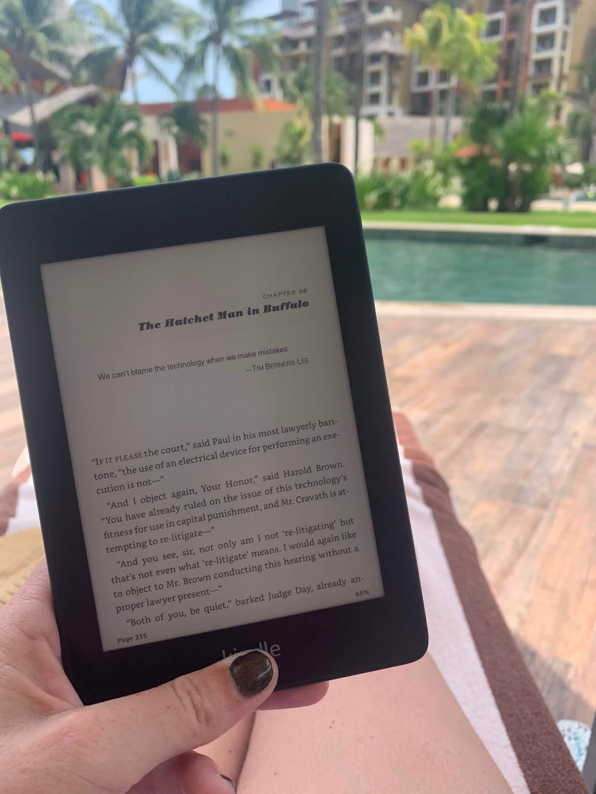 a hand is holding a kindle with the first page of a new chapter showing, there is a pool, lots of greenery, and palm trees in the background