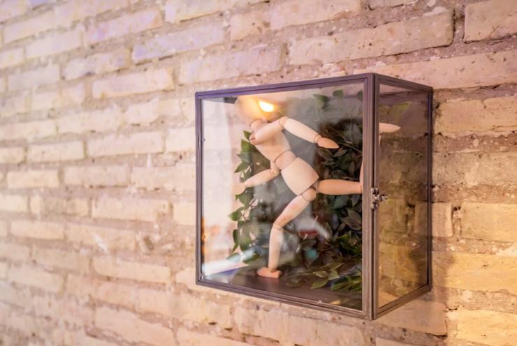 Cómo decorar una casa para alquilar: caja decorativa con figura dentro de urna de cristal sobre pared de ladrillo de cara vista.