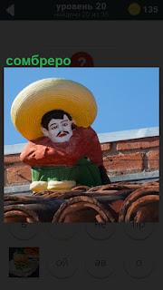 На крыше сидит мужчина с усами в сомбреро, красной рубашке и зеленых штанах