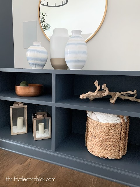 Simple wide bookcases by fireplace