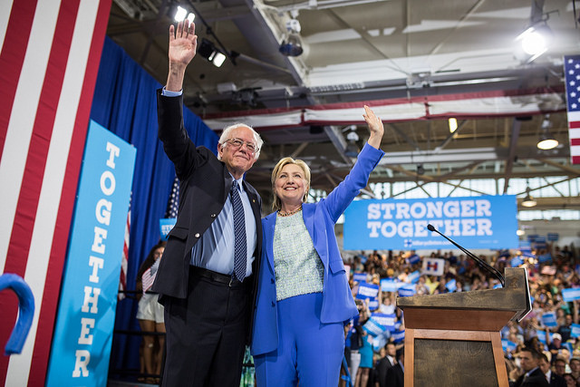 image of Bernie and Hillary campaigning together, standing beside each other, smiling, and waving at the crowd