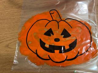 large ziploc bag with jack-o-lantern outline and orange paint inside