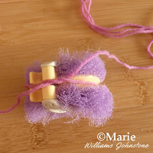 Tying pink yarn around the middle of the purple pom pom