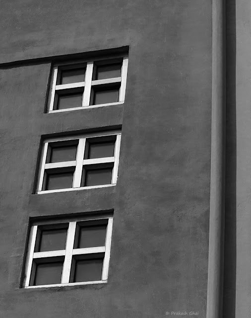 A Black and White Minimal Art Photograph of  Three Windows on a Wall with a Pipe on the side.