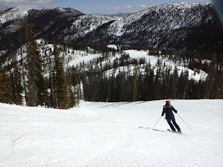 Person skiing down a ski run on a spring day.