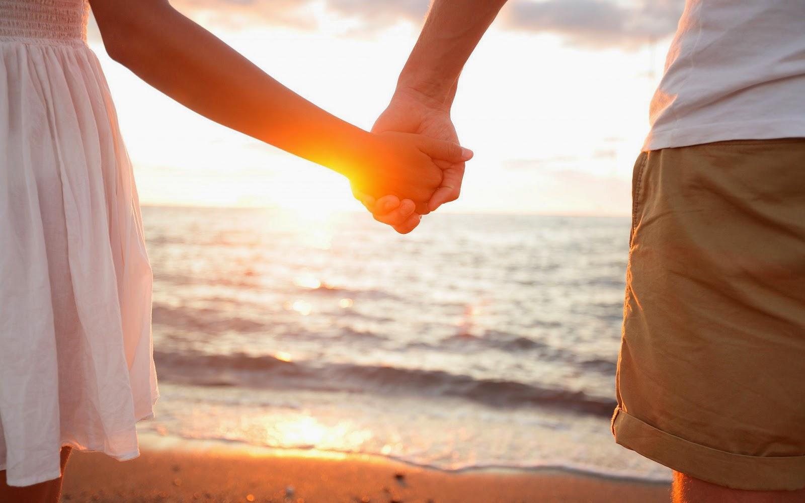 Man en vrouw hand in hand op het strand