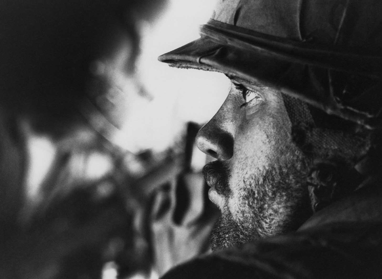 A u s marine with several days of beard growth sits in a helicopter after being picked up from the landing zone near con thein on the southern edge of the
