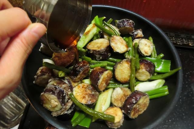いんげんと長ねぎに焼き色がついたら弱火~中火にし、【調味料】をまわし入れ、木べらで全体に行き渡るように混ぜ合わせて煮汁が少なるまで炒め煮にします。