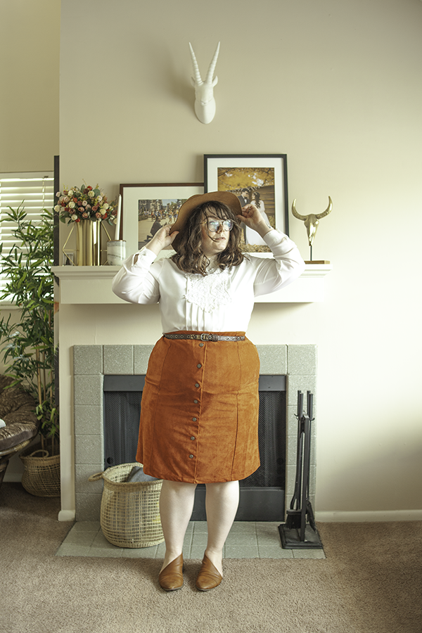 An outfit consisting of a brown panama hat, a white vintage blouse with a lace bib tucked into a burnt orange button down knee length skirt and brown d'orsay flats.