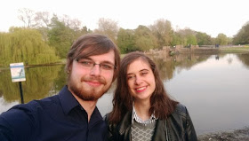 Laura is standing in front of a lake with her partner smiling