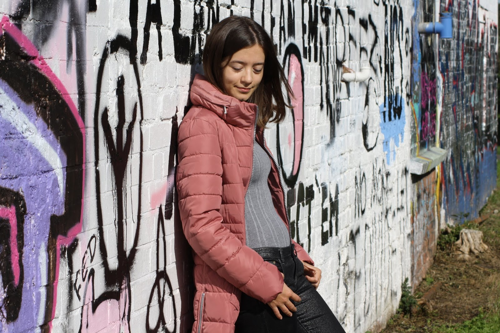 Abbey, wearing a pink puffer jacket, leans on a graffiti wall, looking down