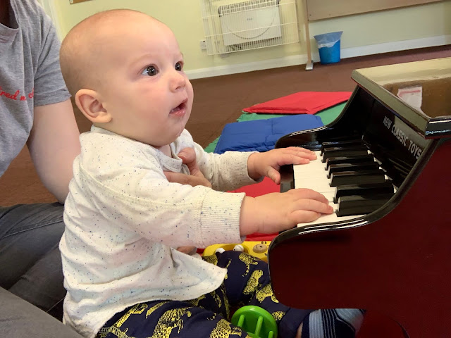5 month old baby boy in a sitting position with some support playing a miniature piano