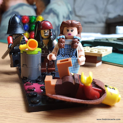 LEGO scene where a knight has knocked over a drink, and Min the Merciless has slipped in it.