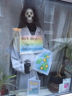 A skeleton wearing a white lab coat and holding a sign 'Bert says...Feeling' hot, hot hot!'