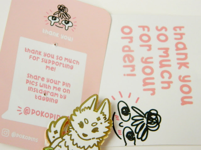 A photo showing a wolf god pin by PokoPins along with some business leaflets