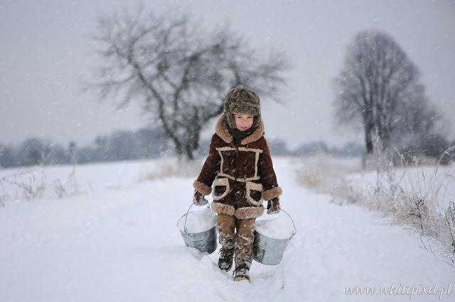 Mały chłopiec na śniegu w Lublinie na sesj zimowej idzie w kożuszku drogą na sankach