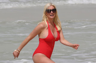 Denise Van Outen channels Baywatch-era Pamela Anderson in plunging red swimsuit on beach