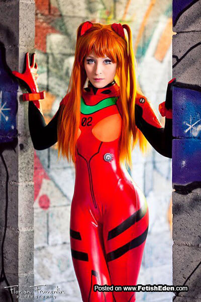 Sexy red-haired girl wears red latex catsuit
