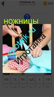 ножницами женщина режет ткань на столе 18 уровень 400 плюс слов 2