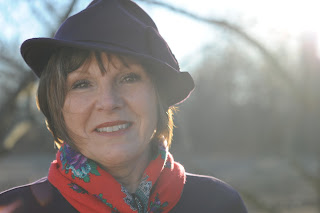 author LoRee Perry is shown wearing black hat and red floral scarf