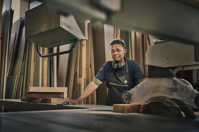 Image of a female woodworker using a dimension saw
