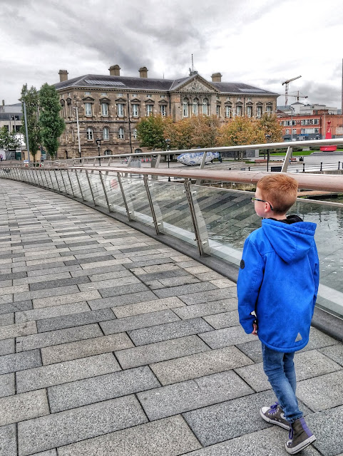 On the lower right hand side a blonde haired boy with black glasses wearing a blue winter coat, blue wash skinny jeans and a pair of grey and purple converse boots is walking across a stone slab lined bridge with glass side panels and a wooden hand rail.  You can see the river through the glass panels. Above the bridge you can see a fish shaped sculpture of blue and white with a historic building in the background backed by grey clouds and surrounded by trees with the colours of autumn showing in the leaves. Cranes and other buildings can be seen in the distance.