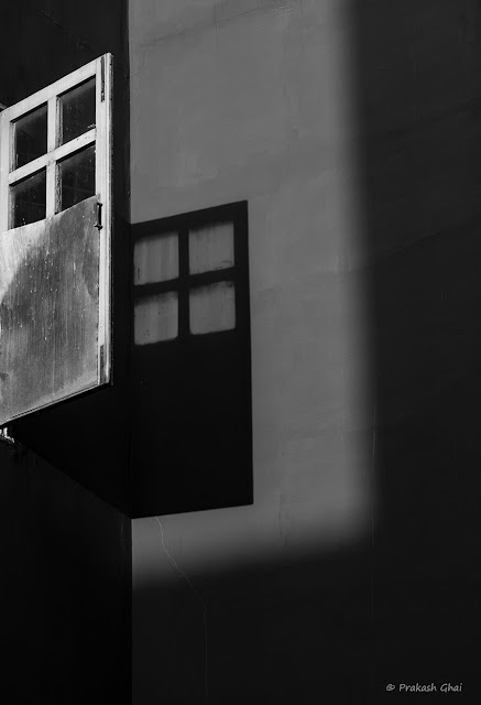 A Black and White Looking Up Minimal Art Photograph of an Open Window with Squares and its Shadow falling on a Wall, at Jawahar Kala Kendra, Jaipur.
