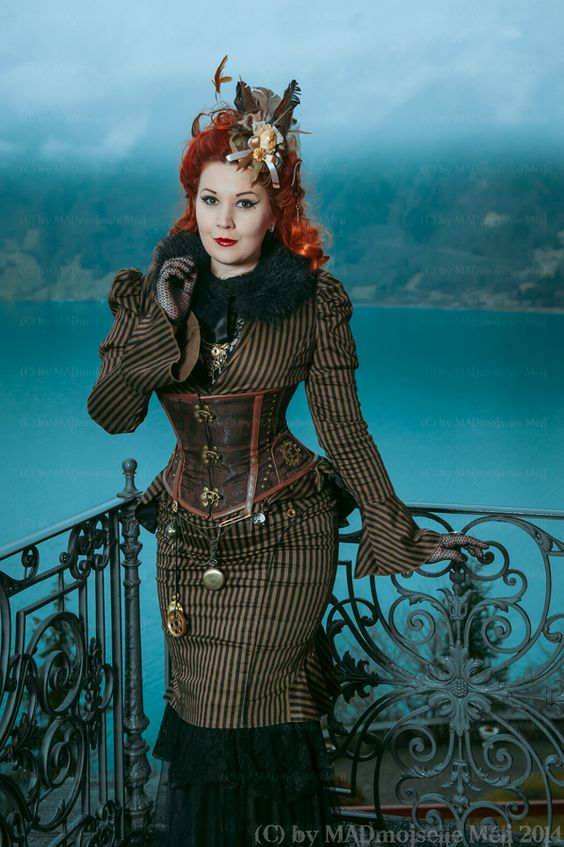 Redhead woman wearing 2 piece suit (matching striped trumpet skirt and jacket) with a brown underbust corset, pocket watch, fur collar and feather fascinator. Steampunk fashion for women