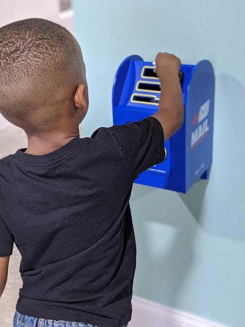 preschool boy pretending to mail letters