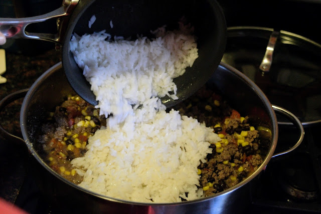 The cooked rice being added to the skillet.