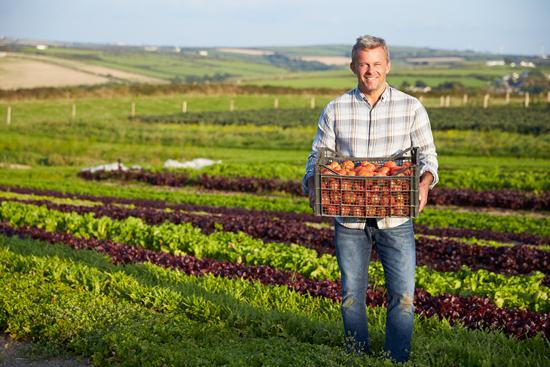 Farmer in field holding non GMO food