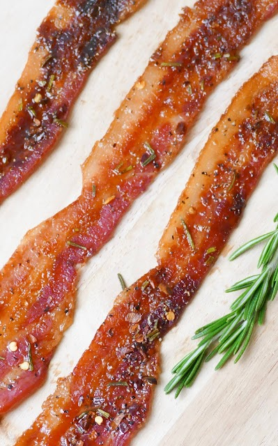 fresh rosemary and bacon on a wooden cutting board.