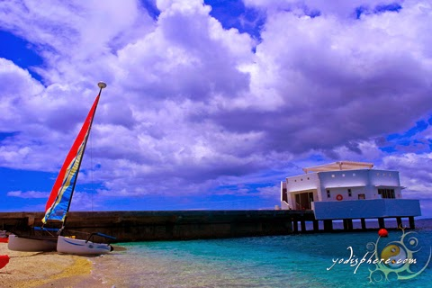 Picturesque Bellarocca dock with boat and colorful sail against blue sky